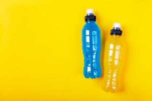 two bottles of flavored water against yellow background