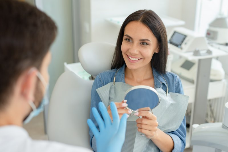 Woman smiling at cosmetic dentist while holding mirror
